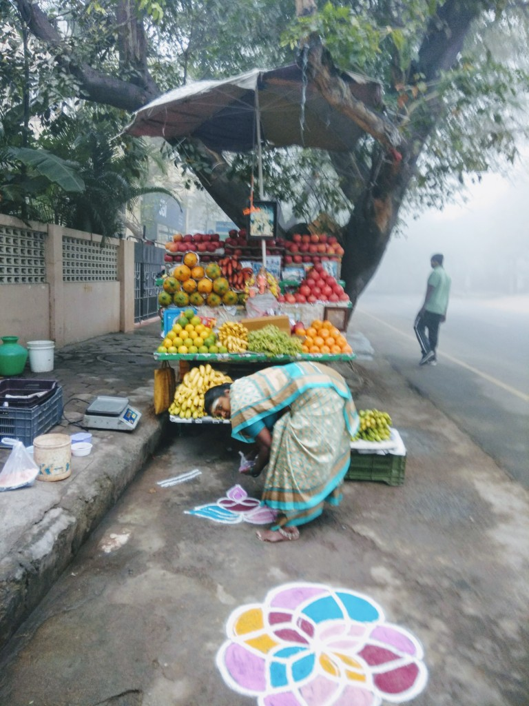 Fruit vendor starts the day with a colourful kolam